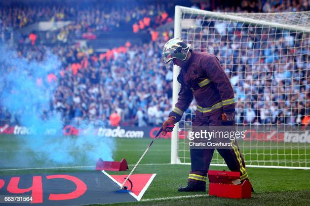 A fire safety officer removes a flare from the pitch after Coventry fans threw them on as they celebrate the teams first goal during the EFL...