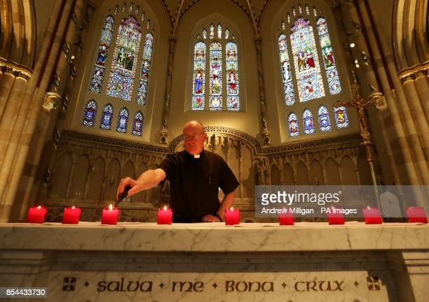 Fire Service Chaplain Father Jim Thomson lights a candle in St Andrews Cathedral for the nine people who lost their lives in the Clutha bar...