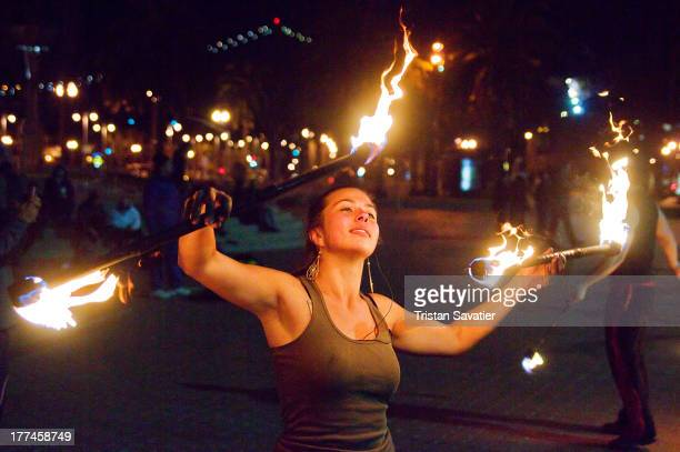 Fire spinning performer practicing with double fire staff.