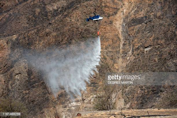 A fire squad helicopter drops water over an area affected by wildfires in Tejeda in Gran Canaria on the Spanish Canary Islands on August 13 2019...