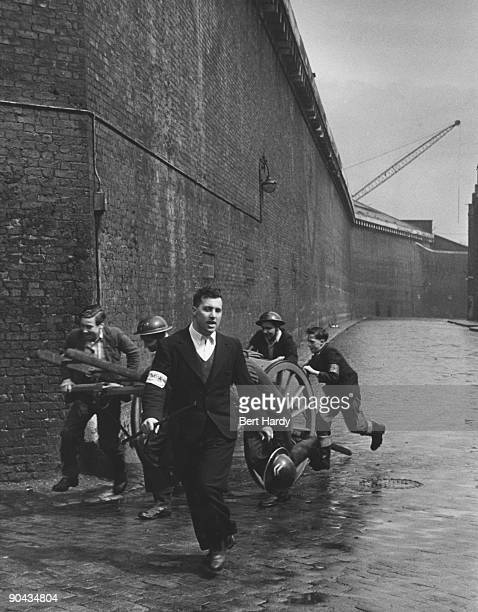 A fire squad rushes along a dock wall in the East End of London to the scene of a fire after an air raid during the Blitz April 1941 The group are...