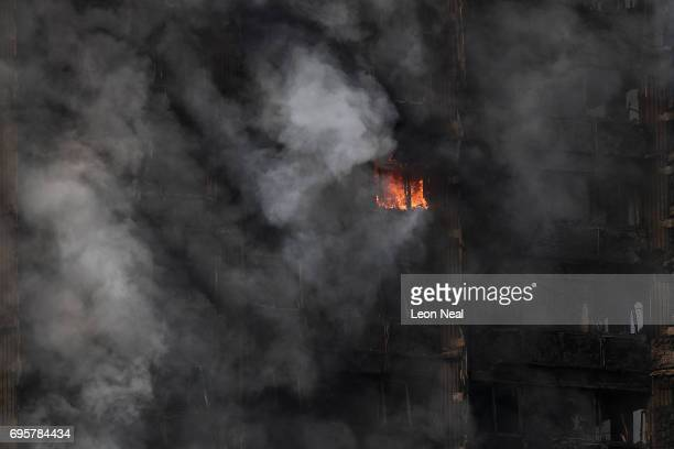 A fire still burns and smoke rises from the building after a huge fire engulfed the 24 storey residential Grenfell Tower block in Latimer Road West...
