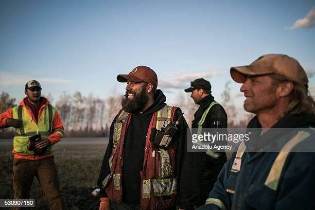 Fire support crew members take a short break during a wildfire that erupted outside Fort McMurray Alberta Canada on May 11 2016 Wildfire erupted on 3...