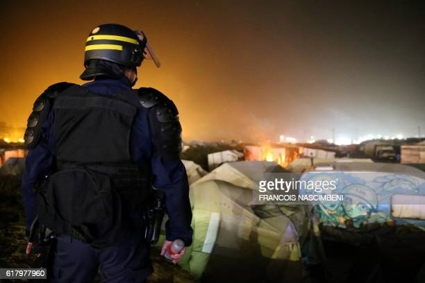 TOPSHOT Fire to keep migrants warm at night burn as a French officer stands on guard at the Calais 'Jungle' camp in Calais northern France on October...