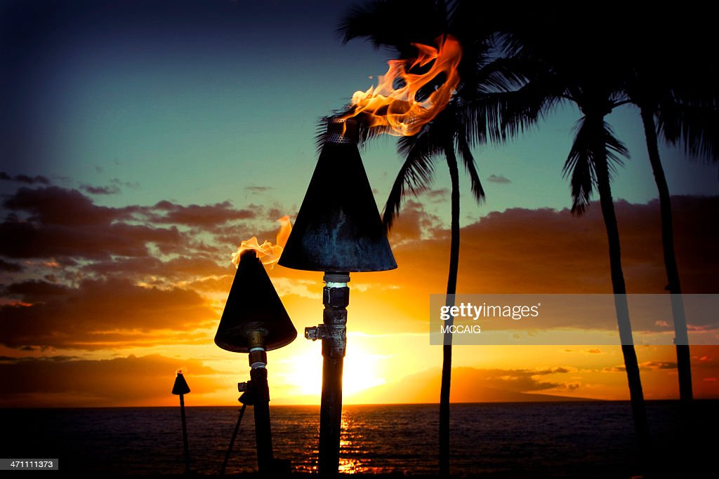 Fire torches against a beautiful island sunset : Stock Photo