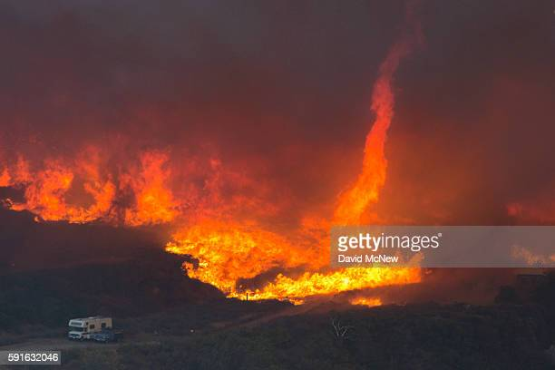 A fire tornado forms near cars parked on a country road at the Blue Cut Fire on August 17 2016 near Wrightwood California An unknown number of homes...