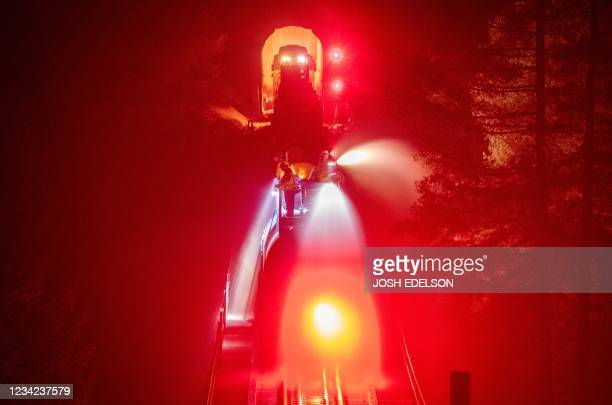 Fire train sprays water along railroad tracks during the Dixie fire in unincorporated Plumas County on July 26, 2021. - The Dixie fire has now burned...