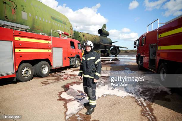 fire training, fireman by fire engines at training facility, portrait - international firefighters day stock pictures, royalty-free photos & images