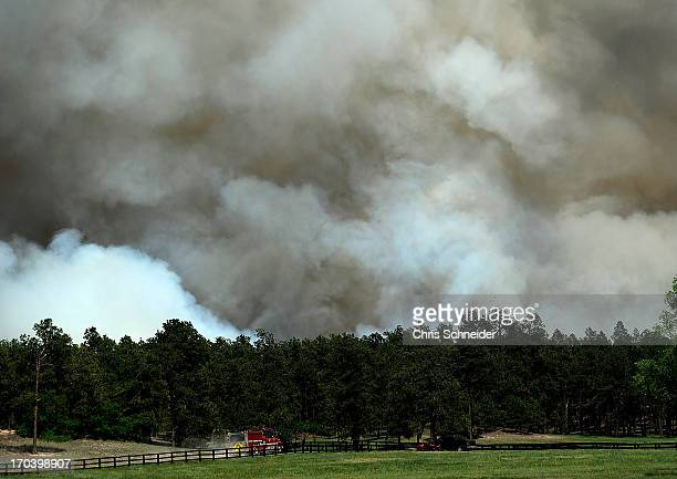 A fire truck approaches a wall of smoke from the Black Forest Fire on June 12 2013 north of Colorado Springs Colorado The fire has reportedly burned...