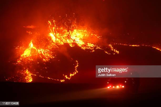 A fire truck drives by a burning hillside as the Kincade Fire burns a hillside on October 24 2019 in Geyserville California Fueled by high winds the...