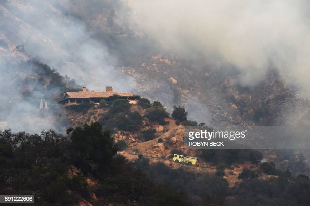 A fire truck drives up Romero Canyon to a house surrounded by smoke from the Thomas Fire in Montecito California on December 12 2017 Crews battling...