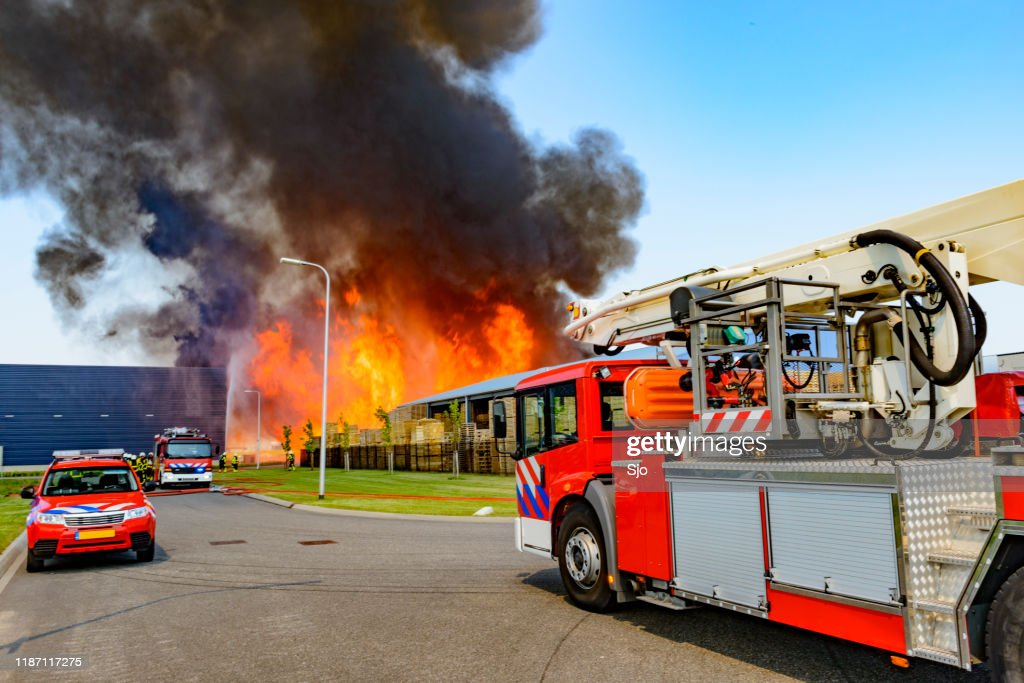 Fire truck in front of a large fire in a factory in an industrial area : Stock Photo
