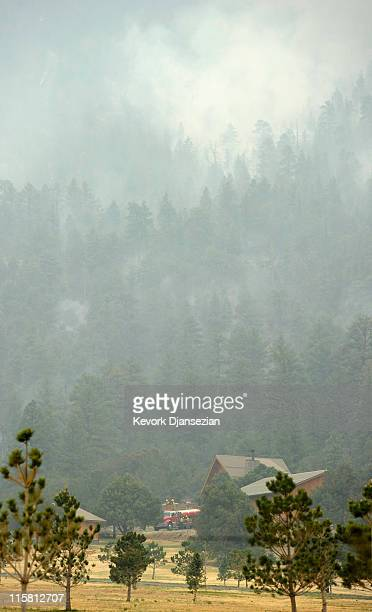 A fire truck in the distance protects a home as the Wallow Fire burns in the hillside along US Highway 191 on June 10 in Nutrioso Arizona The fire...