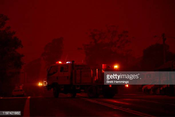 Fire truck leaves the local RFS station as thick smoke turns the town into darkness on January 04, 2020 in Bodalla, Australia. A state of emergency...