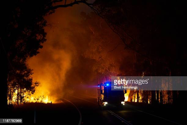 A fire truck passes through a bushfire along Putty Road on November 15 2019 in Colo Heights Australia The warning has been issued for a 80000hectare...