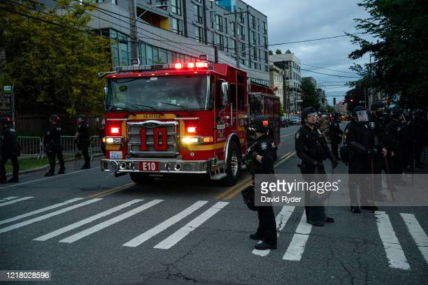 Fire truck passes through police barricades as demonstrators face off with law enforcement personnel near the Seattle Police Departments East...