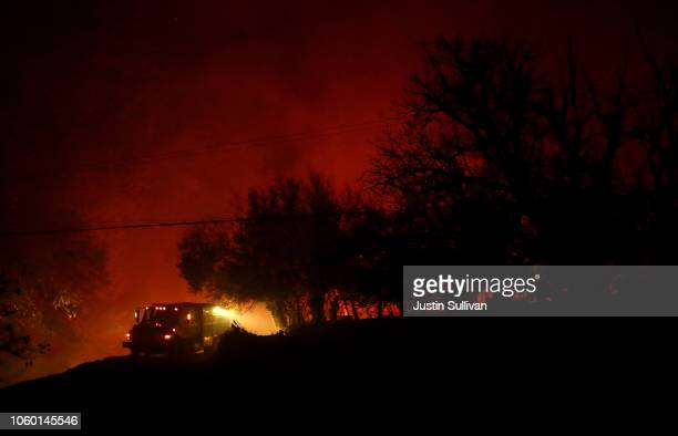 A fire truck stands by as the Camp Fire burns in the hills on November 11 2018 near Oroville California Fueled by high winds and low humidity the...