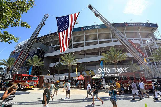 Fire trucks display an American flag from their ladders prior to the game between the Jacksonville Jaguars and Green Bay Packers at EverBank Field on...