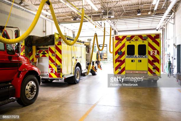 fire trucks in fire station - fire station stock photos and pictures