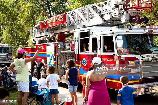 fire trucks in july 4th parade. local community. spectators waving. - fire station stock photos and pictures