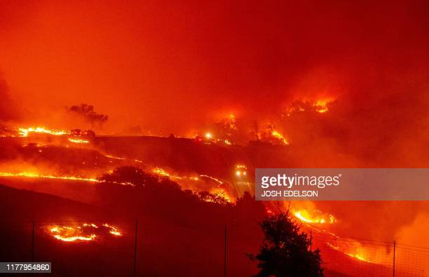 TOPSHOT Fire trucks navigate roads surrounded with fire as wind and embers rip through the area during the Kincade fire near Geyserville California...