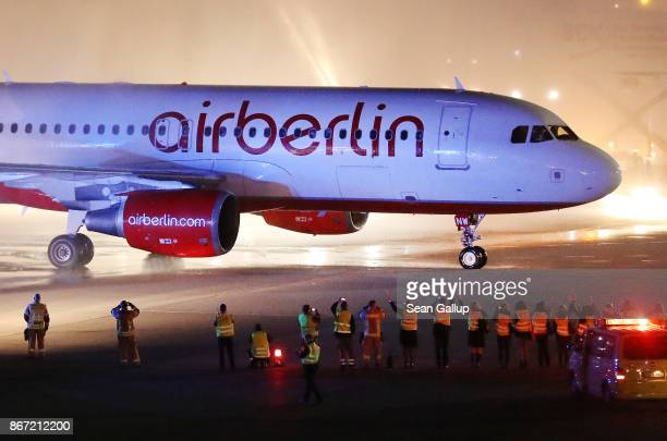 Fire trucks shoot ceremonial bursts of water as ground crews wave to celebrate the arrival of Air Berlin flight AB 6210 from Munich at Tegel Airport...