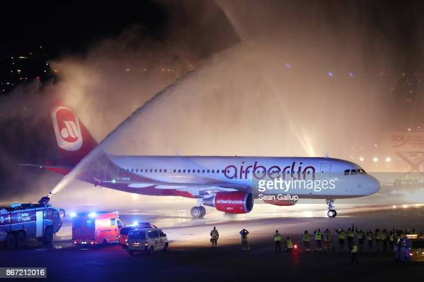 Fire trucks shoot ceremonial bursts of water to celebrate the arrival of Air Berlin flight AB 6210 from Munich at Tegel Airport on October 27 2017 in...