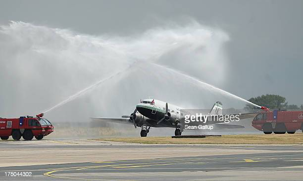 Fire trucks spray water in celebration over a vintage DC3 plane that once participated n the Berlin Airlift and will be part of the Candy Bomber...