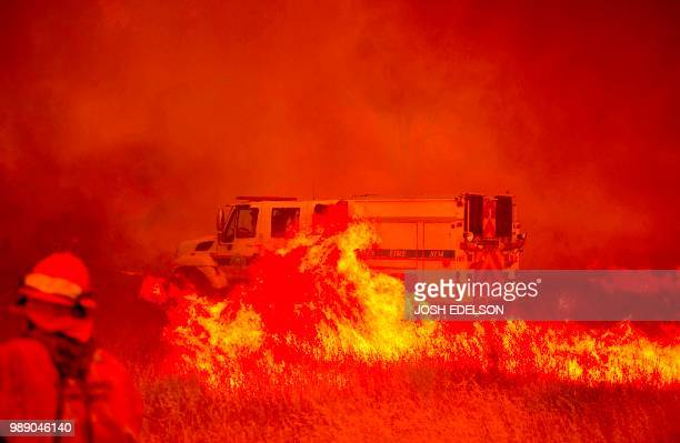 A fire vehicle is surrounded by flames as the Pawnee fire jumps across highway 20 near Clearlake Oaks California on July 1 2018 More than 30000 acres...