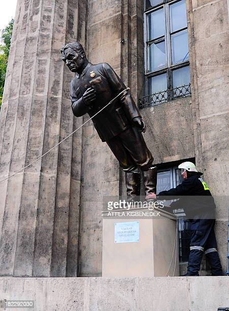 A fire worker controls the temporary pedestal as activists and sympathizers of Hungarian 'Szolidaritas' Movement pull their ropes to break down their...