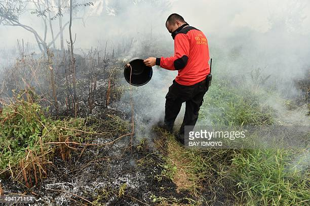 A fire worker helps to extinguish a fire on peat land in Kuala Kapuas Central Kalimantan on October 25 2015 Indonesia has put warships on standby to...