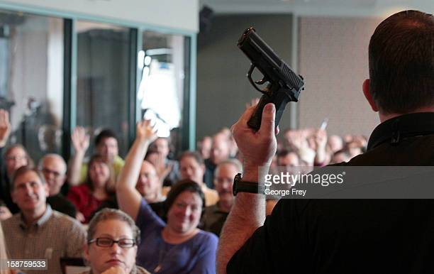 Firearm instructor Clark Aposhian holds a handgun up as he teaches a concealedweapons training class to 200 Utah teachers on December 27 2012 in West...