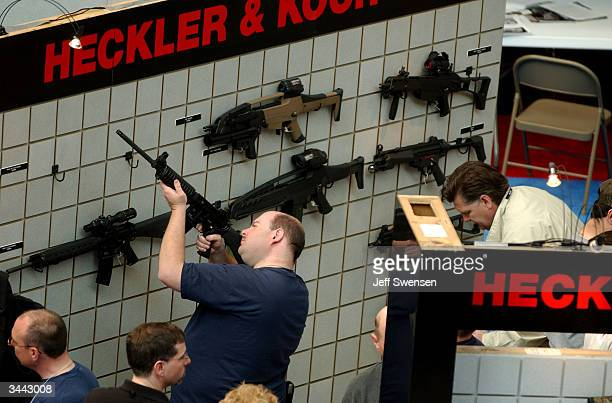 A firearms enthusiast inspects the sights on a tactical assault rifle at the Heckler Koch booth at the 133rd Annual National Rifle Association...