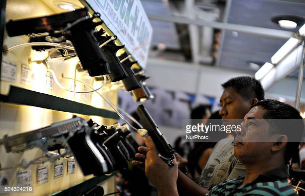 Firearms enthusiasts check out different handguns during the Defense and Sporting Arms Show in Mandaluyong city Metro Manila Philippines July 18 2013...