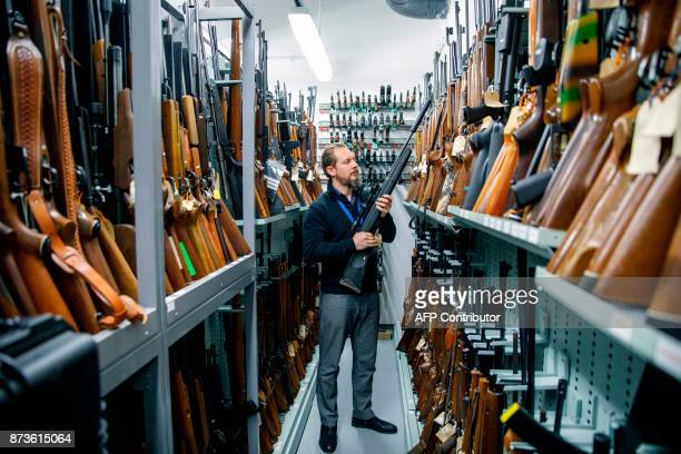 A firearms inspector poses for a photograph with seized and handed in firearms at the storage room of the London Metropolitan Police firearm...