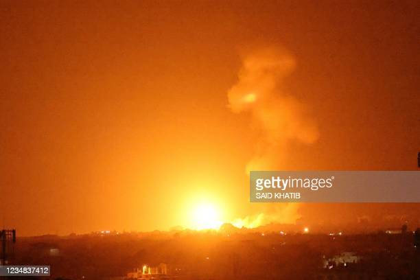 Fireball rises following an air strike in Khan Yunis in the southern Gaza Strip, late on August 23, 2021. - Israel launched airstrikes against Gaza,...
