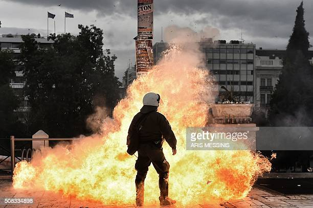 TOPSHOT A firebomb explodes beside a riot police member during a massive protest on February 4 2016 Thousands of people marched across Greece on...