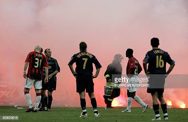 A firebrigader collects fireworks as InterMilan' and AC Milan's players wait for smoke to clear after fans threw fireworks onto the field during the...