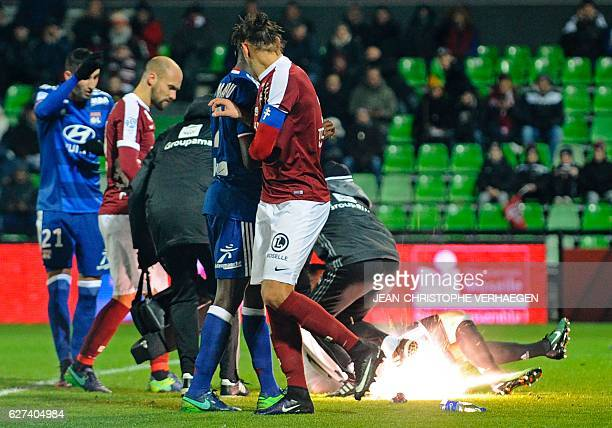 A firecracker explodes beside Lyon and Metz players during the French L1 football match between Metz and Lyon on December 3 2016 at Saint Symphorien...