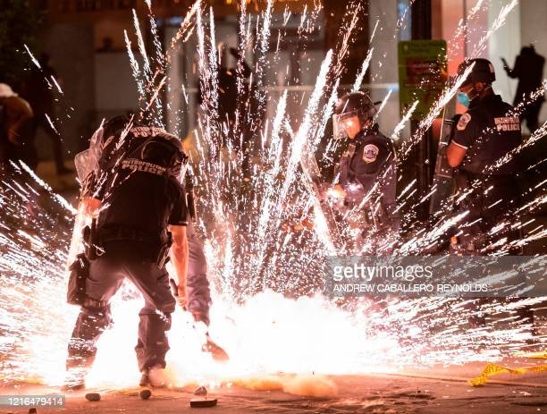 Firecracker thrown by protesters explodes under police one block from the White House on May 30, 2020 in Washington DC, during a protest over the...