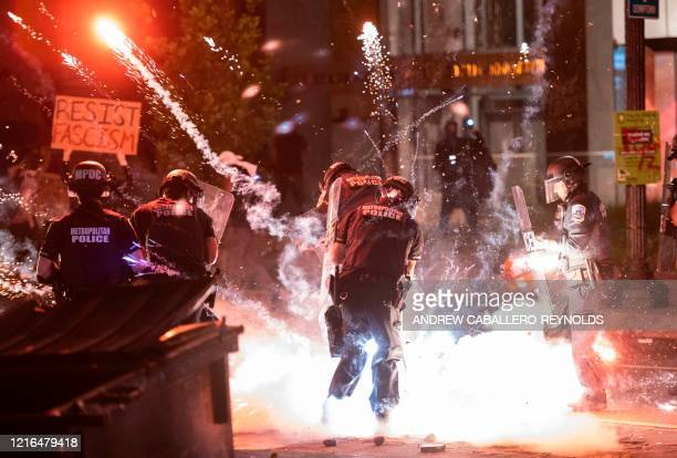 A firecracker thrown by protesters explodes under police one block from the White House on May 30 2020 in Washington DC during a protest over the...