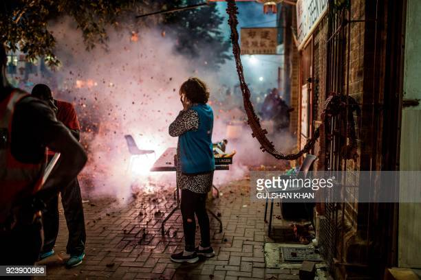 TOPSHOT Firecrackers are set off outside each store to ward off evil spirits during celebrations marking the Chinese New Year the Year of the Dog in...