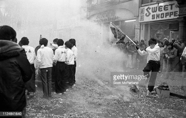 Firecrackers explode around a performer who waves a flag during the annual Chinese New Year celebrations on Mott Street in the Chinatown neighborhood...