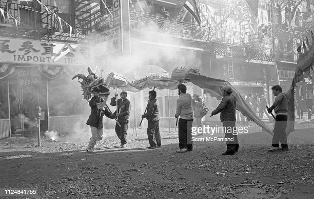 Firecrackers explode around dancers as they perform a traditional Dragon Dance during the annual Chinese New Year celebrations on Mott Street in the...