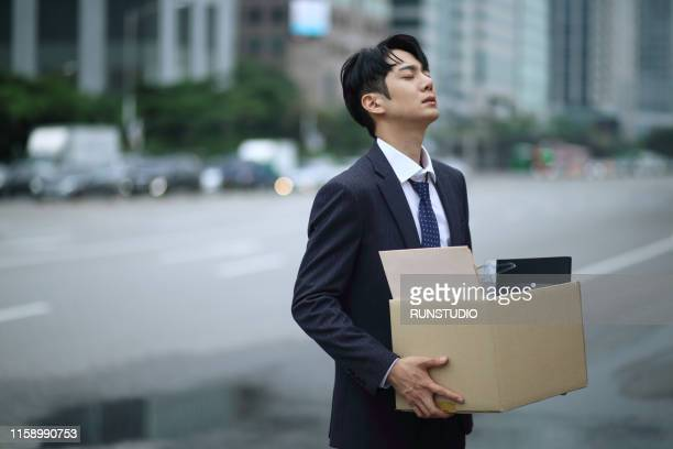 fired businessman carrying box of personal items on street - quitting a job stock pictures, royalty-free photos & images