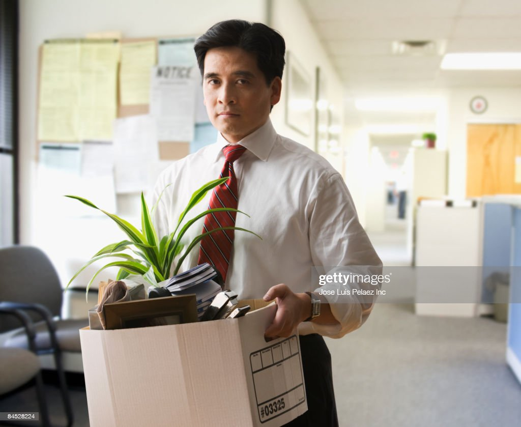 Fired Chinese businessman carrying box of personal items : Stock Photo