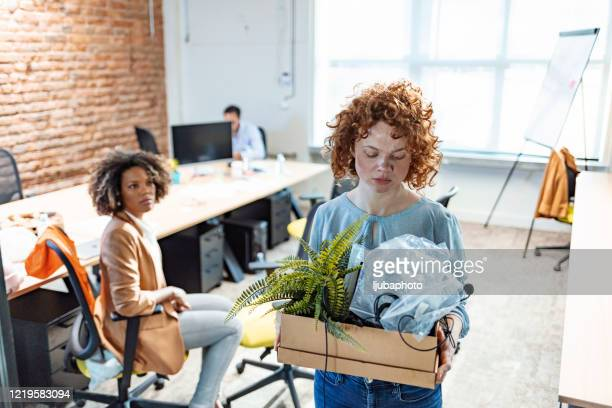 fired female employee holding box of belongings in an office - being fired stock pictures, royalty-free photos & images
