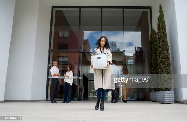 fired woman leaving the office with her belongings in a box - quitting a job stock pictures, royalty-free photos & images