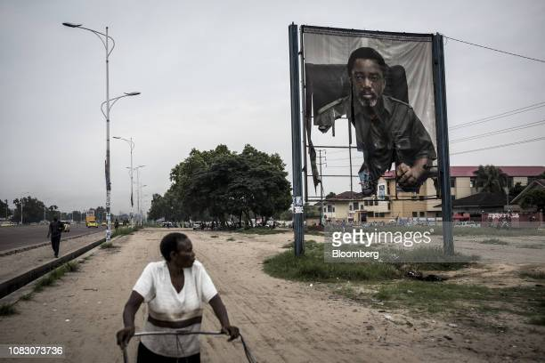 A firedamaged banner featuring Joseph Kabila Congo's outgoing president stands by the roadside in Kinshasa Democratic Republic of the Congo on Friday...