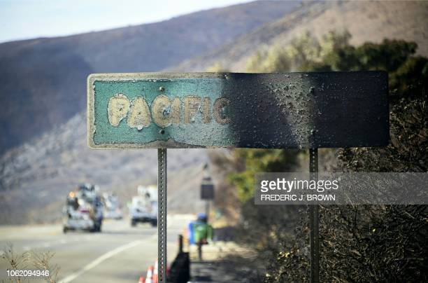 A firedamaged Pacific Coast sign remains standing along the Pacific Coast Highway amid the blackened and charred hills from the Woolsey Fire in...